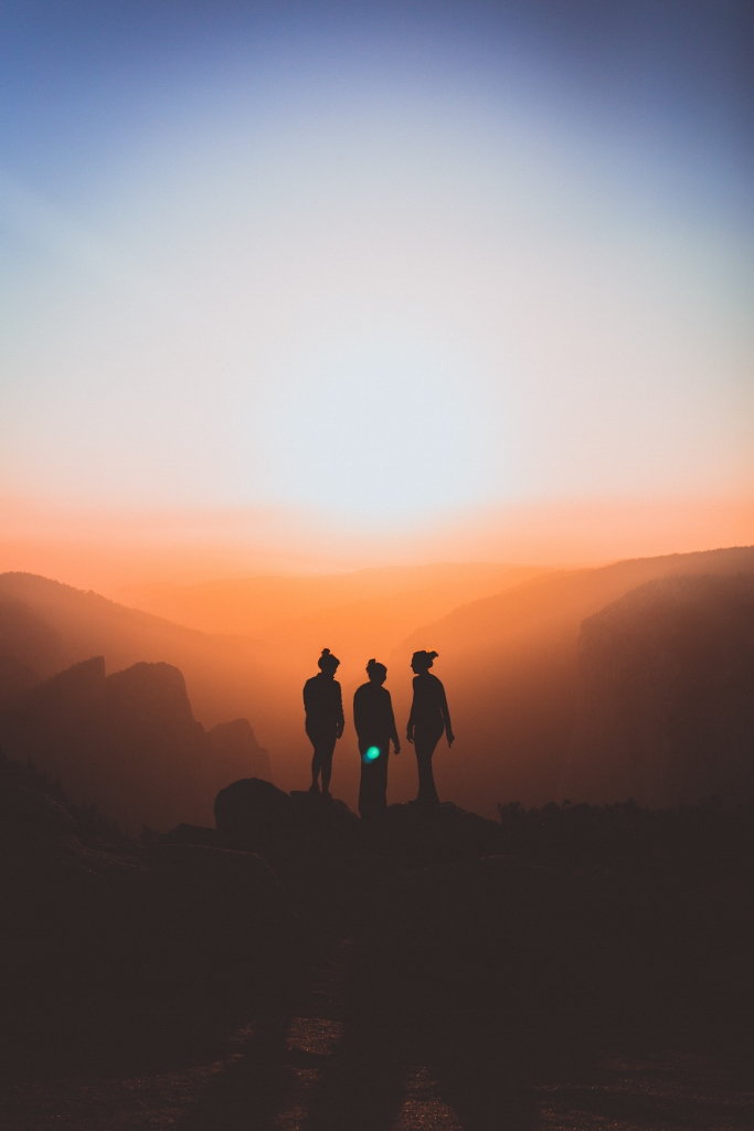 Group of people standing on mountain overlooking hazy sunrise
